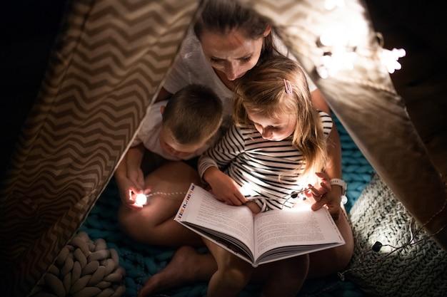 Vue de dessus de la mère avec des enfants assis à l'intérieur dans la chambre, lisant un livre.