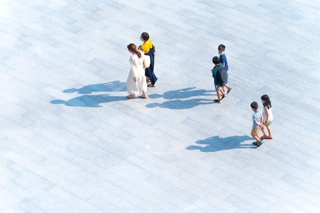 Vue de dessus des mères et des enfants de la famille du groupe marchant sur une passerelle piétonne en plein air