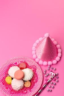 Une vue de dessus des meringues et marmelades à l'intérieur de la plaque avec des sifflets d'anniversaire et un chapeau d'anniversaire sur rose, couleur douce de sucre de guimauve