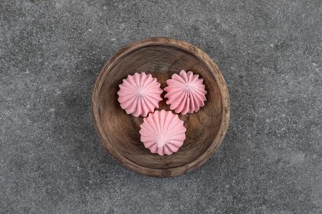 Vue de dessus des meringues rouges dans un bol en bois sur une surface grise
