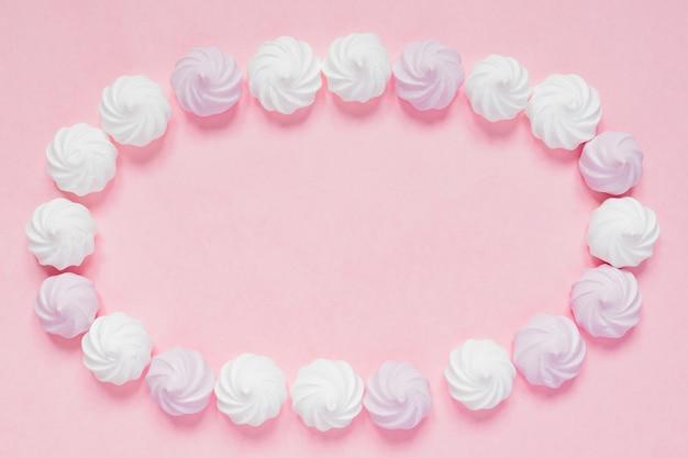 Vue de dessus des meringues torsadées blanches et roses sur fond rose