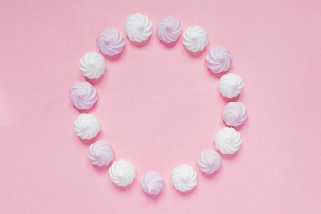 Vue de dessus des meringues torsadées blanches et roses sur rose