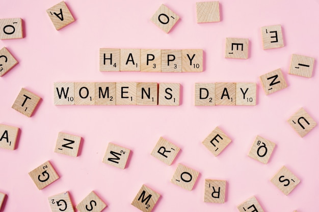 Vue de dessus message woomans jour heureux orthographié dans des blocs de bois sur fond rose