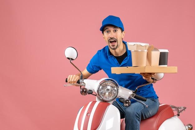 Vue de dessus d'un messager émotionnel choqué portant un chapeau assis sur un scooter sur fond de pêche pastel