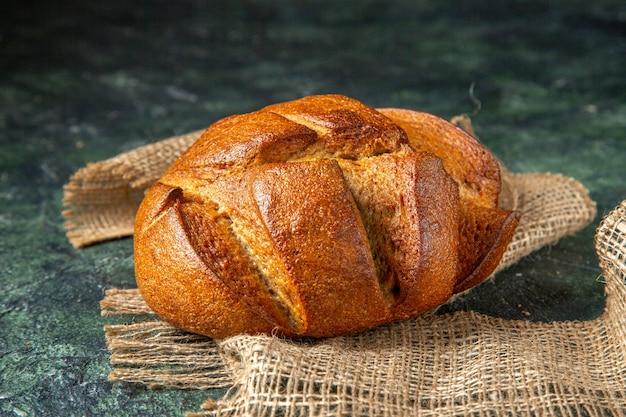 Vue de dessus d'une miche de pain noir diététique sur une serviette brune sur une surface de couleurs foncées avec un espace libre