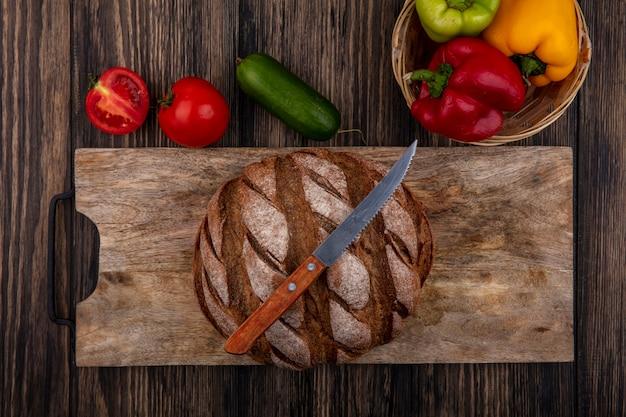 Vue de dessus miche de pain noir sur un support avec un couteau avec des tomates concombre et poivrons sur un fond en bois