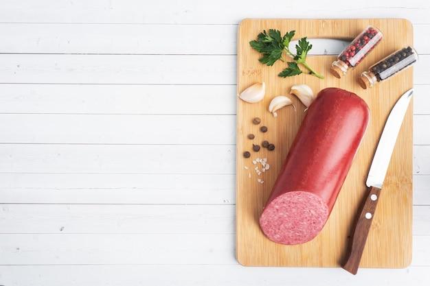 Vue de dessus d'une miche de saucisse de salami sur une planche à découper sur fond de bois blanc