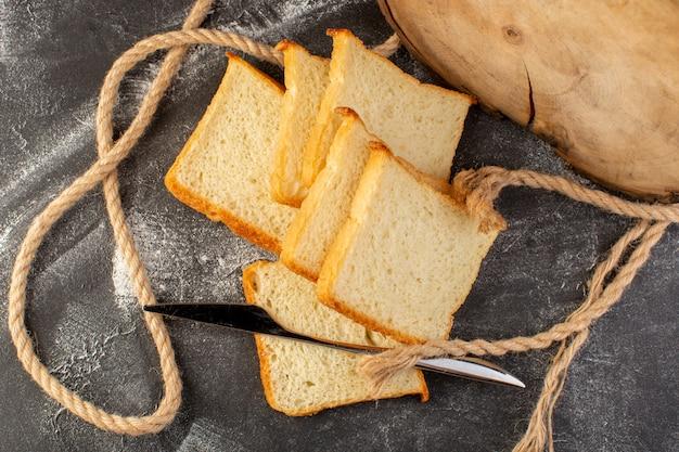 Vue de dessus des miches de pain blanc en tranches et savoureux isolés avec des cordes et un couteau sur le fond gris pâte à pain pain alimentaire