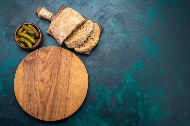 Vue de dessus des miches de pain avec des cornichons sur un bureau bleu foncé.