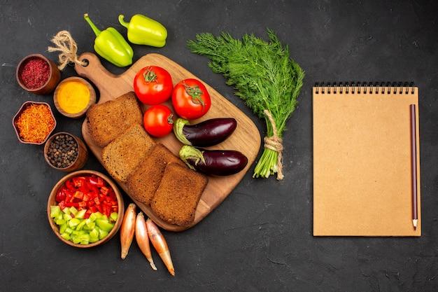 Vue de dessus des miches de pain noir avec assaisonnements tomates et aubergines sur fond sombre salade santé repas mûr régime végétal