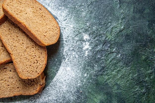 Vue de dessus des miches de pain noir sur un bureau sombre