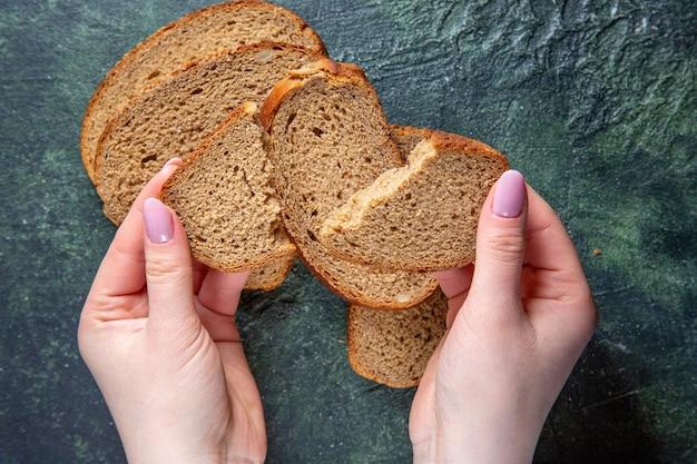 Vue de dessus des miches de pain noir avec déchirure féminine sur un bureau sombre
