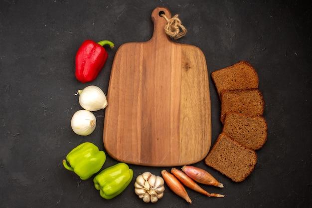 Vue de dessus des miches de pain noir avec des légumes sur un espace sombre
