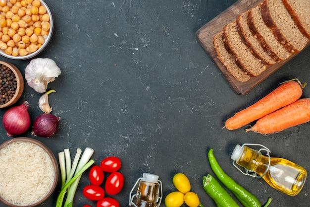 Vue de dessus des miches de pain noir avec des légumes sur fond gris foncé