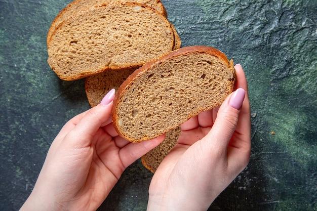 Vue de dessus des miches de pain noir avec des mains féminines sur un bureau sombre