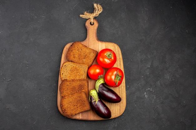 Vue de dessus des miches de pain noir avec des tomates et des aubergines sur fond sombre salade santé repas mûr