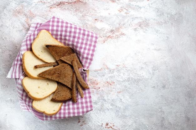 Vue de dessus des miches de pain en tranches de morceaux de pain sur un bureau blanc