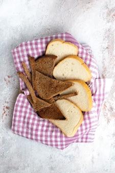 Vue de dessus des miches de pain en tranches de morceaux de pain sur la pâte de nourriture de pain de bureau blanc