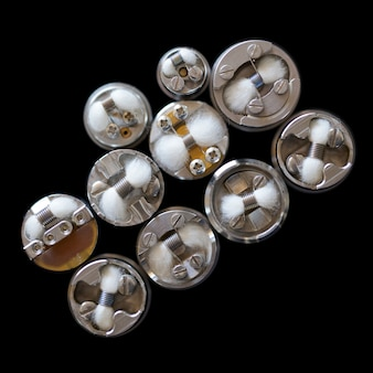 Vue de dessus de micro bobine unique avec du coton dans des atomiseurs dégouttants reconstructibles isolés sur fond noir