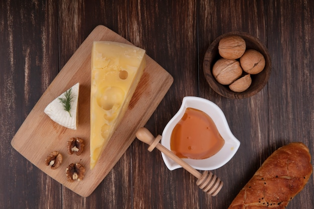 Vue de dessus le miel dans une soucoupe avec une variété de fromages sur un support avec des noix et une miche de pain sur un fond en bois