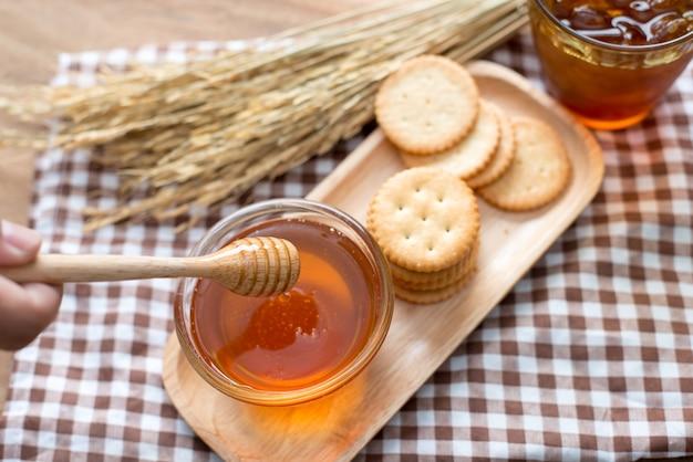 Vue de dessus de miel, louche en bois de miel et de citron sur le plateau de bois sur fond de bois blanc.