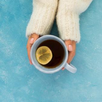 Vue de dessus mignon thé d'hiver tenu par les mains de la femme