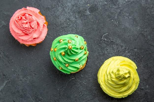 Vue de dessus de mini cupcakes colorés en rangée diagonale sur fond sombre