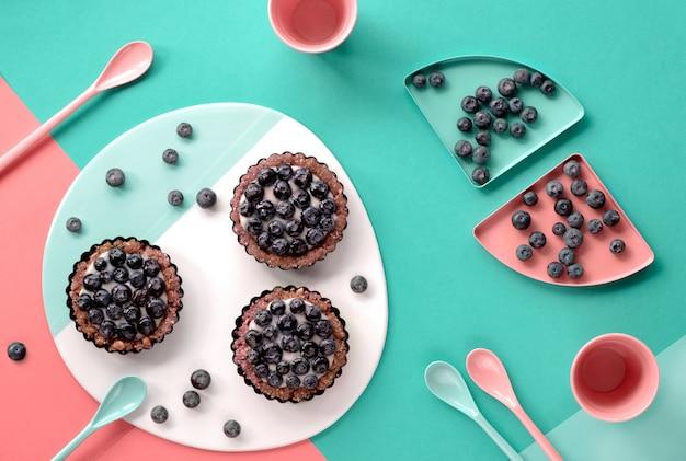 Vue de dessus sur les mini gâteaux aux bleuets, à plat sur la menthe fendue et le mur de papier corail