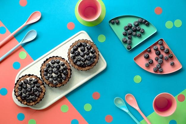 Vue de dessus sur les mini gâteaux à la crème aux myrtilles pour la fête d'anniversaire des enfants