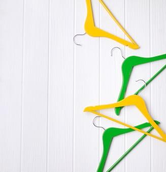 Vue de dessus minimaliste plat poser des cintres en bois jaune, vert au tableau blanc avec espace de copie.