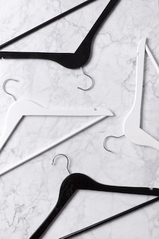 Vue de dessus minimaliste plat poser des cintres en bois noir et blanc à table en marbre