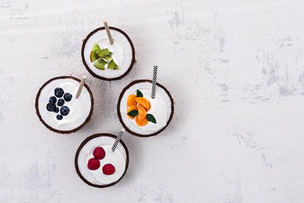 Vue de dessus à la mode quatre bols de smoothies avec des baies et des fruits sur fond blanc