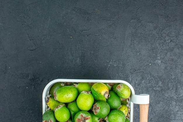 Vue de dessus à moitié frais feijoas sur panier en plastique sur l'espace libre de table sombre