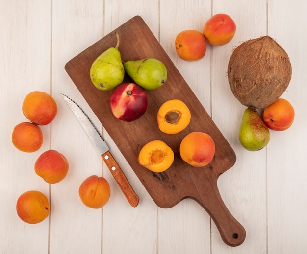 Vue de dessus de la moitié des fruits coupés et entiers comme les abricots de pêche et les poires sur une planche à découper et motif o abricots poire et noix de coco et couteau sur fond de bois