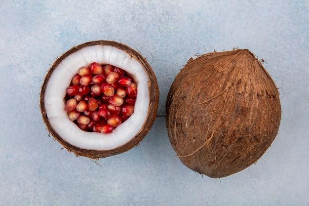 Vue de dessus de la moitié de la noix de coco à l'intérieur des graines de grenade rouge avec grosse noix de coco sur une surface blanche