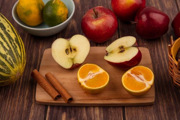 Vue de dessus de la moitié des pommes savoureuses sur une planche de cuisine en bois avec la moitié des mandarines et des bâtons de cannelle avec melon cantaloup aux pommes isolé sur un mur en bois