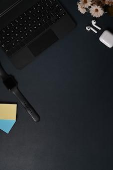 Vue de dessus montre intelligente, ordinateur portable et écouteurs sur cuir noir.