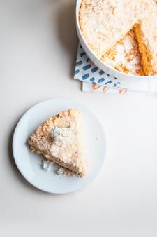 Vue de dessus d'un morceau de gâteau avec du lait caillé sur fond blanc, photo verticale