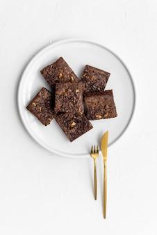 Vue de dessus des morceaux de brownie frais sur plaque blanche avec couverts dorés
