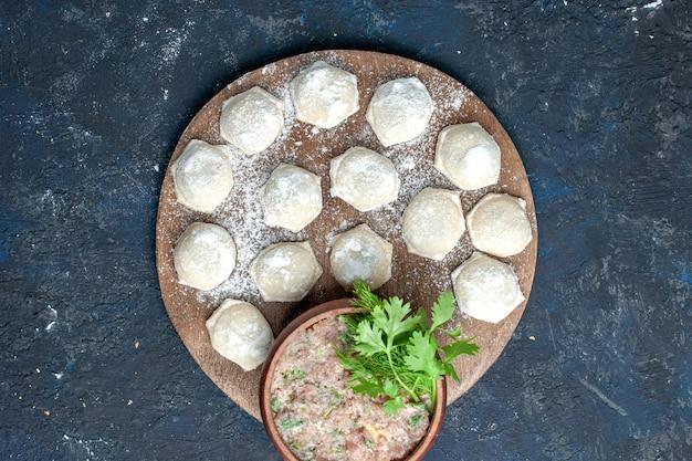 Vue de dessus des morceaux de pâte farinée avec des verts de viande hachée sur des aliments sombres, de la pâte à base de viande crue