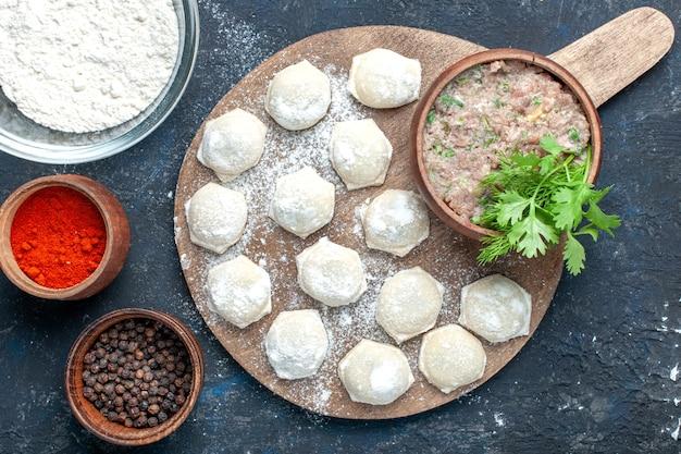 Vue de dessus des morceaux de pâte farinée avec des verts de viande hachée avec du poivre sur des aliments foncés, de la pâte à base de viande crue