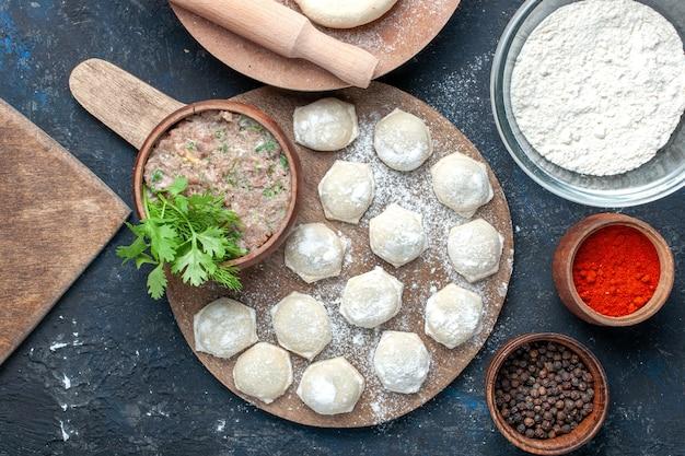 Vue de dessus des morceaux de pâte farinée avec des verts de viande hachée avec du poivre sur un bureau sombre, de la pâte à manger de la viande crue