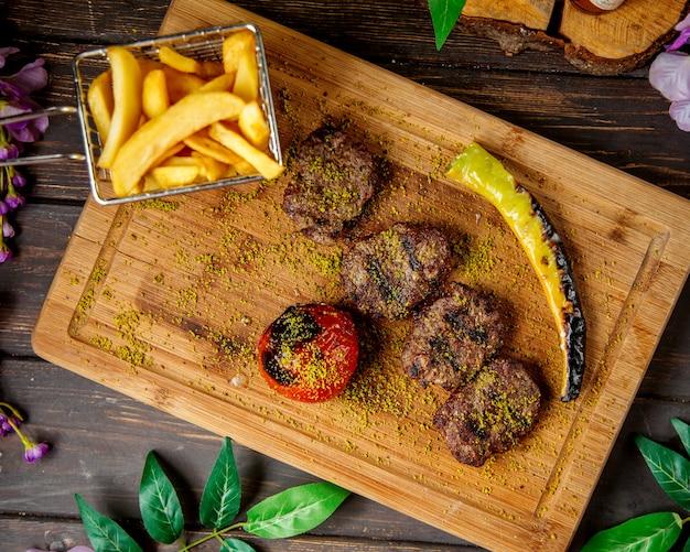 Vue de dessus de morceaux de steak d'agneau servis avec des frites poivrons grillés et tomates
