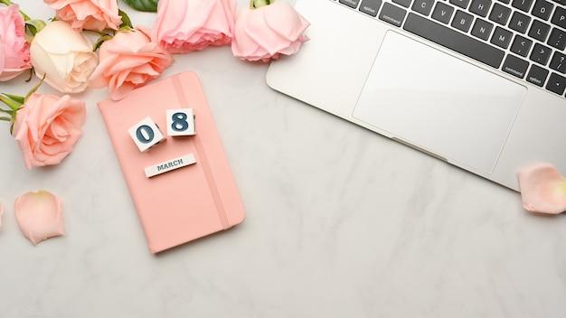 Vue de dessus des dés avec le mot «08 mars» journée de la femme sur le livre de journal, ordinateur portable et fleur sur l'espace de travail