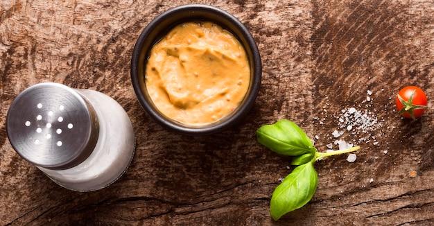Vue de dessus de la moutarde dans un bol avec salière et tomate