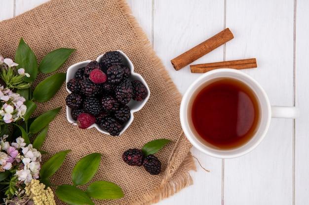 Vue de dessus de la mûre dans un bol avec des fleurs et une tasse de thé à la cannelle sur une surface blanche