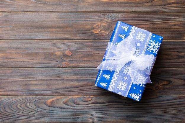 Vue de dessus noël ou autre emballage de boîte présente à la main de vacances, fond plat en bois foncé. boite cadeau