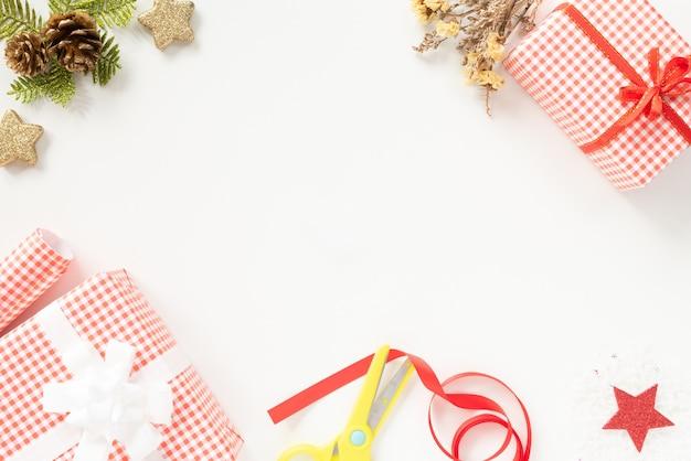 Vue de dessus de noël de boîte de cadeau de noël avec étoile rouge et pommes de pin sur fond blanc.