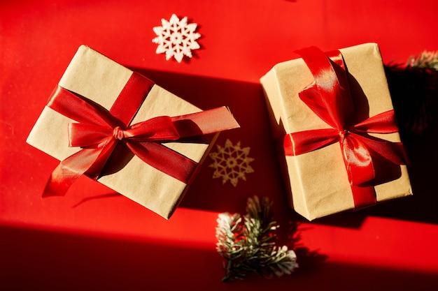 Vue de dessus noël emballage écologique papier kraft et cadeaux de branches de sapin pour la saison des fêtes sur fond rouge, lumière dure