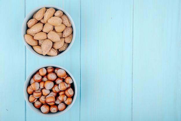 Vue de dessus des noisettes et des amandes en coque dans des bols sur fond de bois bleu avec copie espace